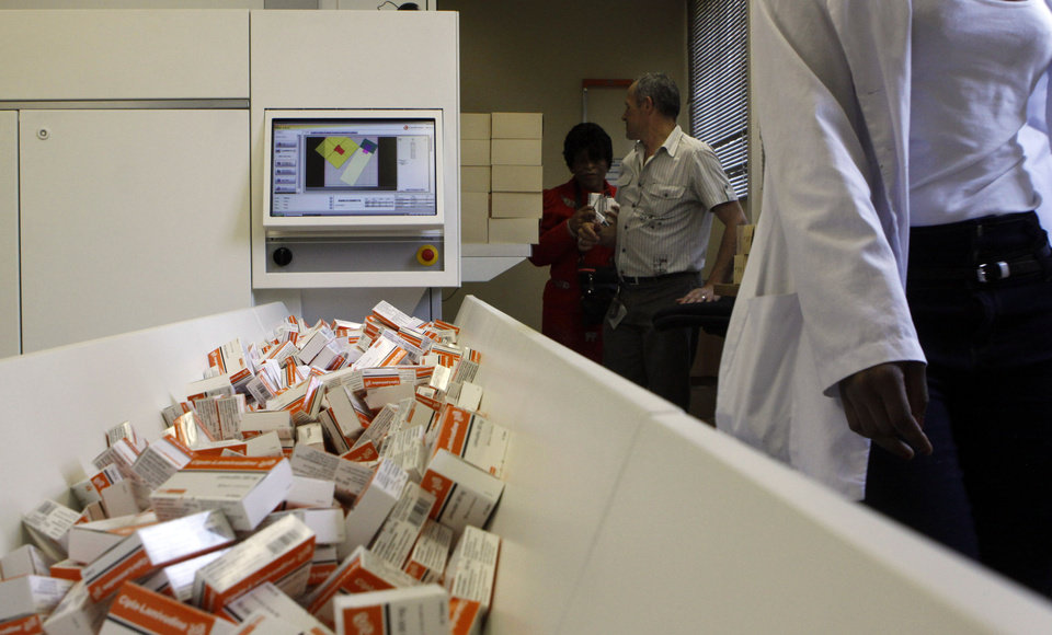 Photo - In this photo taken Thursday, Nov. 15, 2012 a newly mechanized pharmaceutical machine that helps pharmacists dispense medicine is loaded with ARV medication, at the US sponsored Themba Lethu, HIV/AIDS Clinic, at the Helen Joseph hospital, in Johannesburg. In the early 90s when South Africa's Themba Lethu clinic could only treat HIV/AIDS patients for opportunistic diseases, many would come in on wheelchairs and keep coming to the health center until they died. Two decades later the clinic is the biggest ARV (anti-retroviral) treatment center in the country and sees between 600 to 800 patients a day from all over southern Africa. Those who are brought in on wheelchairs, sometimes on the brink of death, get the crucial drugs and often become healthy and are walking within weeks.  (AP Photo/Denis Farrell)