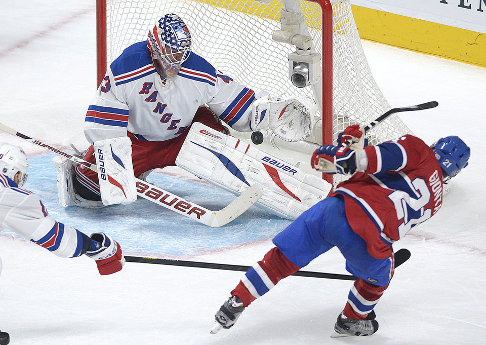 Photo - New York Rangers goaltender Martin Biron, left, makes a save against Montreal Canadiens' Brian Gionta during the second period  of an NHL hockey game in Montreal, Saturday, Feb. 23, 2013. (AP Photo/The Canadian Press, Graham Hughes)