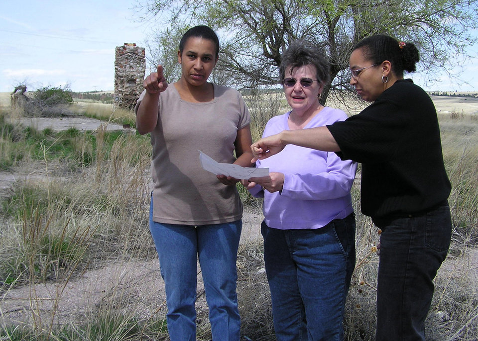 Photo - FILE - In this April 26, 2004 file photo Cheryl Robinson, center, and her two daughters, Desiree Marks, left, and Tamara Kamara read a map outlining various landmarks at Wounded Knee, S.D. Ray Robinson, Cheryl's husband and Desiree and Tamara'a father, is believed to have been killed at the site during a 71-standoff between the American Indian Movement and federal agents in 1973.  Documents recently released by the FBI to a Buffalo, N.Y., lawyer shed new light on the 40-year-old case of Robinson, an activist and follower of Martin Luther King Jr. The FBI says Robinson was killed during the 1973 occupation of Wounded Knee, and it suspects militant members of the American Indian Movement are responsible. His body was never found. (AP Photo/Carson Walker, File)