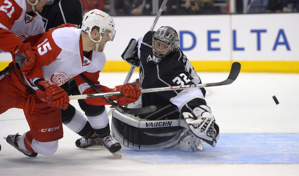 Photo - Detroit Red Wings center Riley Sheahan, left, scores on Los Angeles Kings goalie Jonathan Quick during the first period of an NHL hockey game, Saturday, Jan. 11, 2014, in Los Angeles. (AP Photo/Mark J. Terrill)