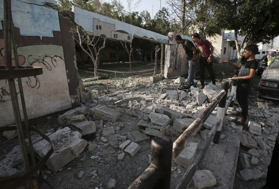 Photo - Palestinians inspect the destroyed wall of Shifa hospital after an Israeli air strike, in Gaza, in the northern Gaza Strip, Monday, July 28, 2014. Israel's Prime Minister Benjamin Netanyahu said in a televised speech Monday that Israelis must be