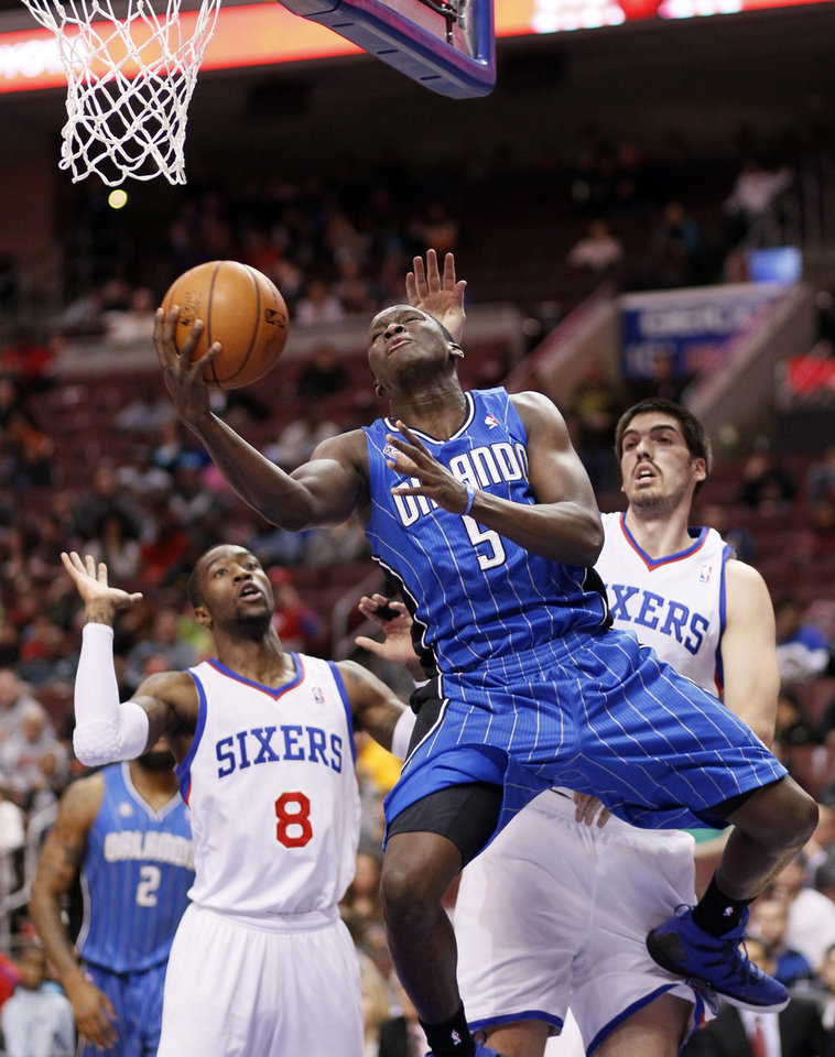 Photo - Orlando Magic's Victor Oladipo, center, drives in for a layup between Philadelphia 76ers' Tony Wroten, left, and Byron Mullens, right, during the first half of an NBA basketball game on Wednesday, Feb 26, 2014, in Philadelphia. (AP Photo/Tom Mihalek)