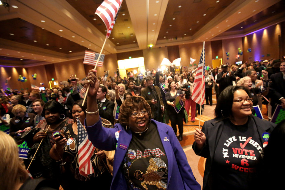 Photo -   Elizabeth Thomas, 62, of Detroit, waves an American flag as she watches results for the election on the screen at the Michigan Democratic Party in the grand ballroom at the MGM Hotel and Casino in Detroit on Tuesday, Nov. 6, 2012. (AP Photo/Detroit Free Press, Kimberly P. Mitchell) DETROIT NEWS OUT; NO SALES