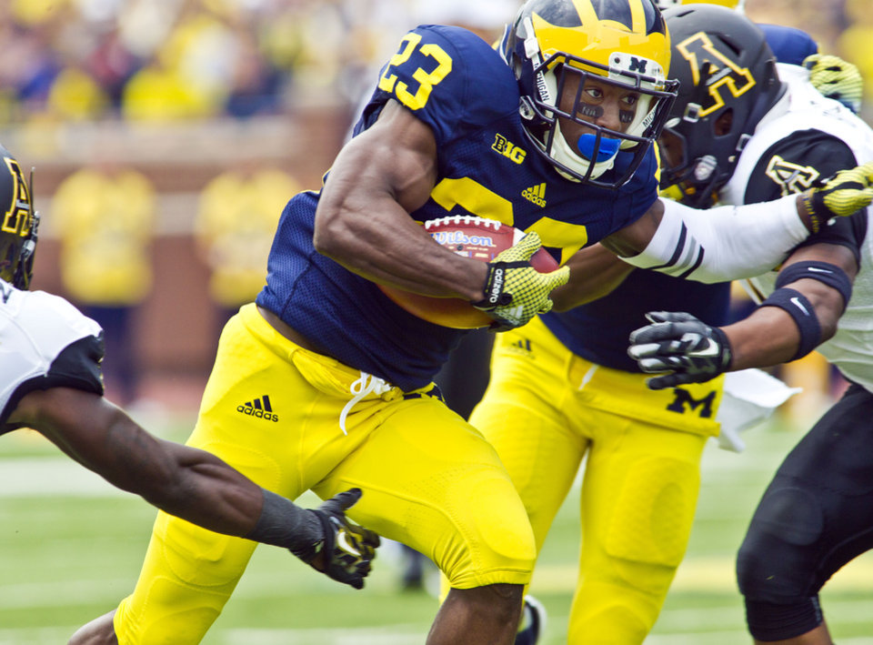 Photo - Michigan wide receiver Dennis Norfleet (23) breaks through Appalachian State defenders in the first quarter of an NCAA college football game in Ann Arbor, Mich., Saturday, Aug. 30, 2014. (AP Photo/Tony Ding)
