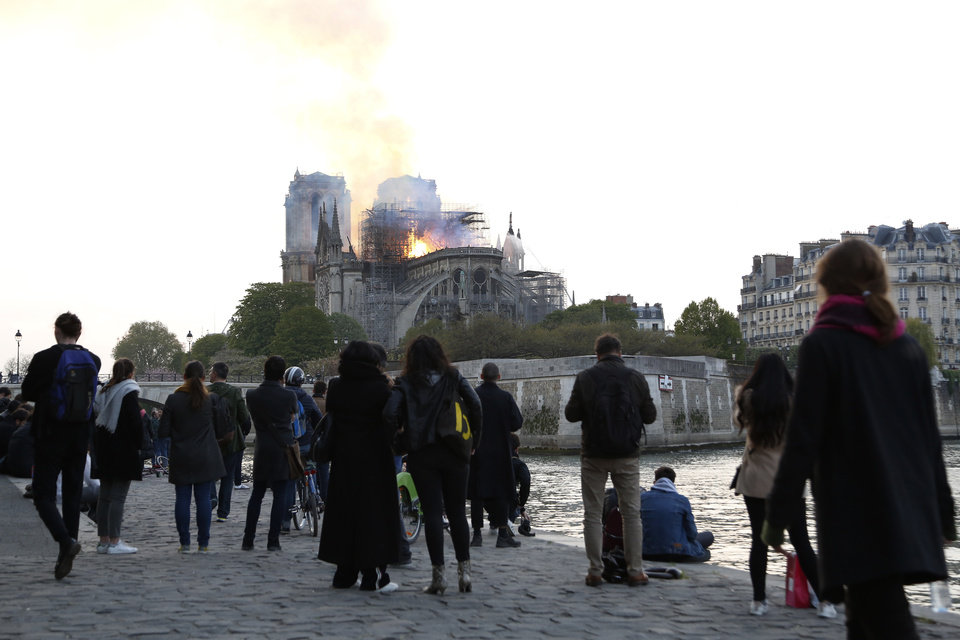 Photo - People standing on the banks of the river Seine watch as flames and smoke rise from Notre Dame cathedral as it burns in Paris, Monday, April 15, 2019. Massive plumes of yellow brown smoke is filling the air above Notre Dame Cathedral and ash is falling on tourists and others around the island that marks the center of Paris. (AP Photo/Thibault Camus)