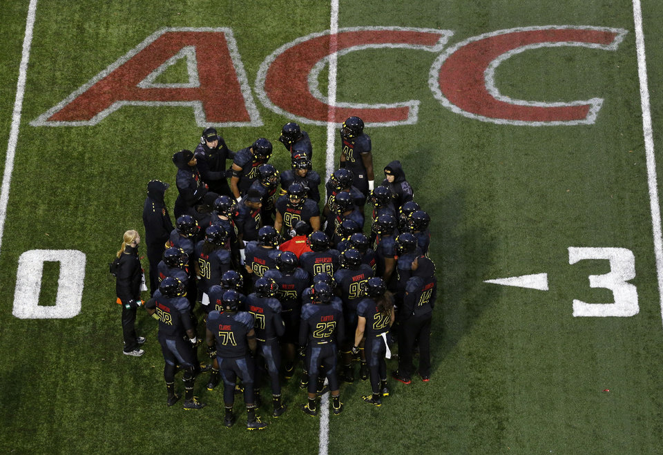 Photo - File-This Nov. 23, 2013, file photo shows members of the Maryland football team huddling in the first half of an NCAA college football game against Boston College in College Park, Md.  The musical chairs of conference realignment returns this this week, with more major colleges taking new seats. On Tuesday, July 1, 2014, 12 FBS teams officially switch places, including Louisville in the Atlantic Coast Conference and Maryland and Rutgers in the Big Ten. (AP Photo/Patrick Semansky, File)