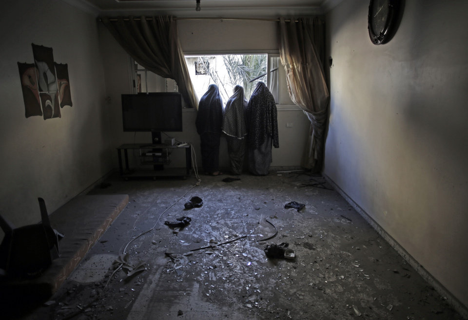 Photo - Palestinian women look outside from the window of their destroyed house, following late night Israeli strikes in Gaza City on Wednesday, Aug. 20, 2014. (AP Photo/Khalil Hamra)