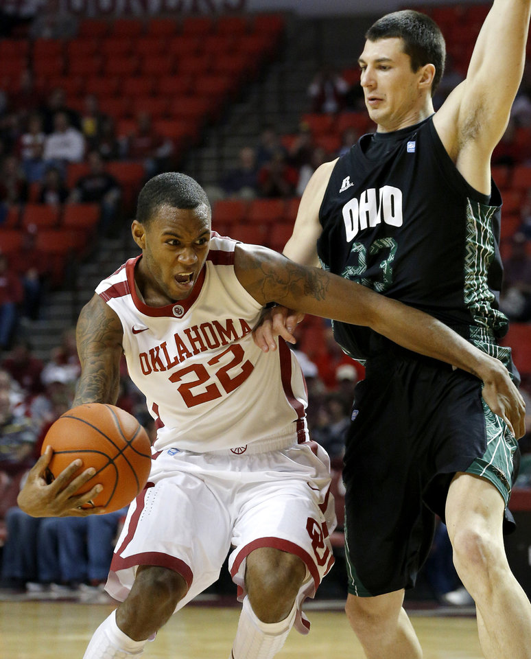 Photo - Oklahoma's Amath M'Baye (22) tires to get past Ohio's Ivo Baltic (23) during a NCAA college basketball game between the University of Oklahoma (OU) and Ohio at the Lloyd Noble Center in Norman, Saturday, Dec. 29, 2012. Photo by Bryan Terry, The Oklahoman