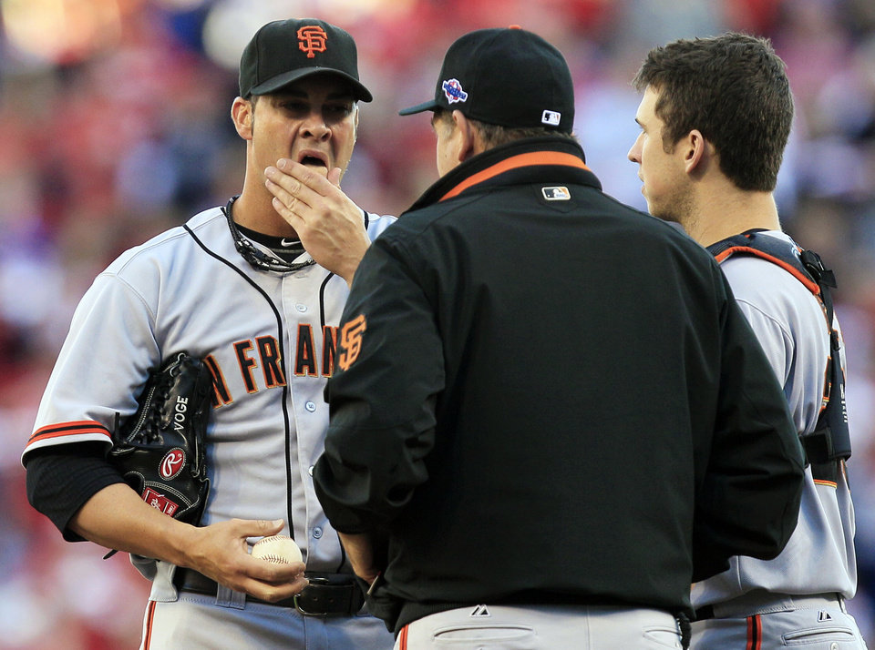 San Francisco Giants starting pitcher Ryan Vogelsong, left, talks with pitching coach Dave Righetti and catcher Buster Posey, right, in the first inning during Game 3 of the National League division baseball series against the Cincinnati Reds, Tuesday, Oct. 9, 2012, in Cincinnati. (AP Photo/Al Behrman)