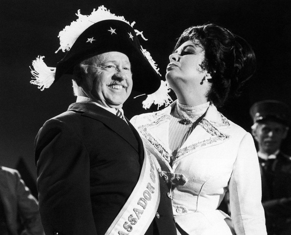 """Photo - FILE - In this Thursday, Aug. 27, 1981, file photo, veteran comic Mickey Rooney wears a Napoleonic-era hat as he tapes an """"I love New York"""" television commercial with British-American actress Elizabeth Taylor, in New York. Rooney, a Hollywood legend whose career spanned more than 80 years, has died. He was 93. Los Angeles Police Commander Andrew Smith said that Rooney was with his family when he died Sunday, April 6, 2014, at his North Hollywood home. (AP Photo/GPB, File)"""