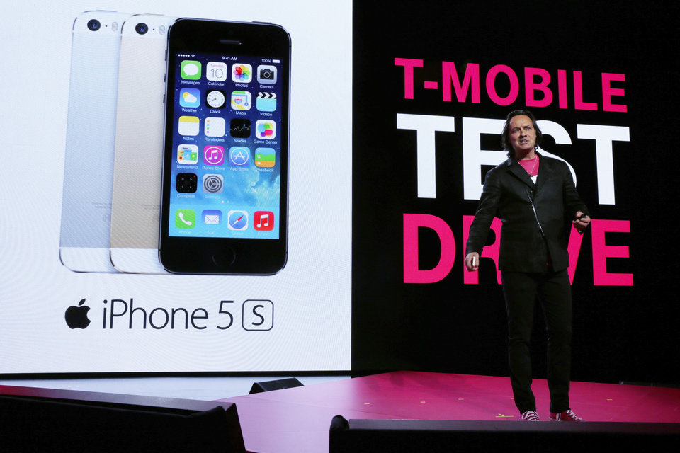 Photo - T-Mobile CEO John Legere talks about his company's new program that offers a free seven-day test drive of an Apple iPhone 5S at T-Mobile's Uncarrier 5.0 event, Wednesday, June 18, 2014, in Seattle. (AP Photo/Ted S. Warren)
