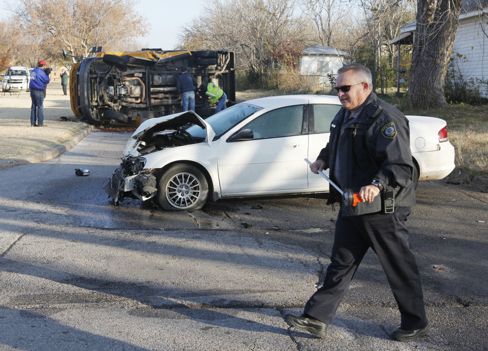 Emergency workers investigate an accident involving a school bus and a car Tuesday at the intersection of NW 89 and Classen Boulevard in Oklahoma City. Photo By Paul Hellstern, The Oklahoman