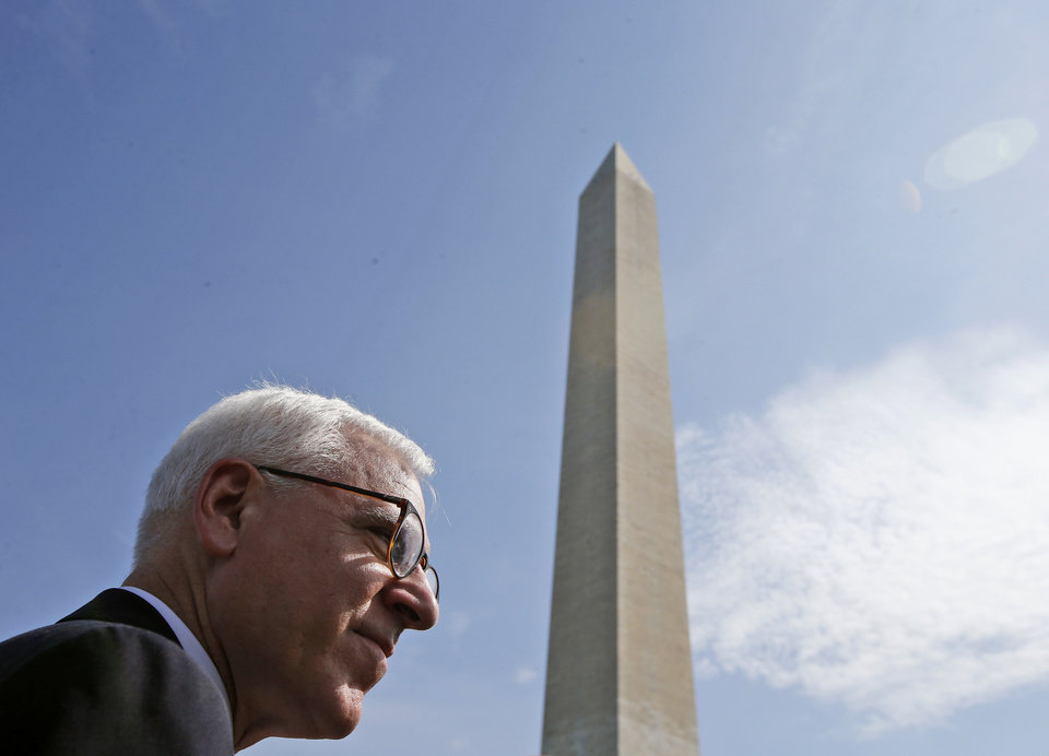 Photo - David M. Rubenstein, co-founder and co-chief executive officer of The Carlyle Group, stands at the Washington Monument in Washington, Monday, May 12, 2014, before a ceremony to celebrate its re-opening. The monument, which sustained damage from an earthquake in August 2011, reopened to the public today. (AP Photo)