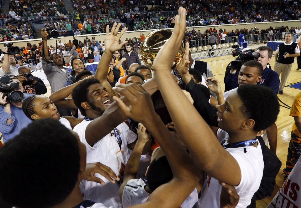 Photo - Deondre Clark and teammates hoist the championship trophy as Douglass defeats the Stilwell Indians 78-50 in the finals of the State Class 4A Boys Basketball Tournament at the Fairgrounds Arena on Saturday, March 15, 2014, in Oklahoma City, Okla. Photo by Steve Sisney, The Oklahoman