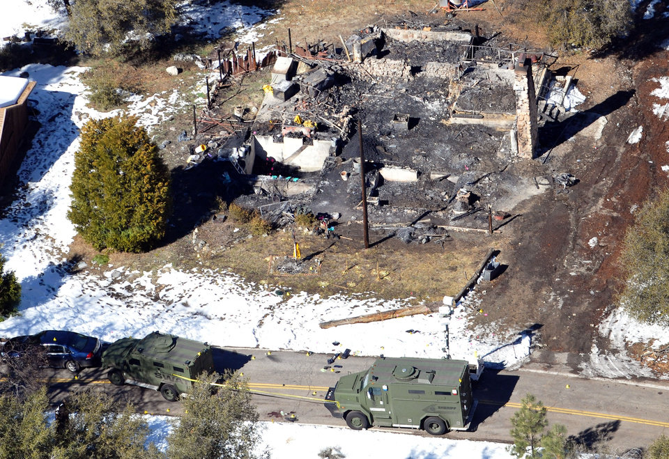 In this aerial photo, law enforcement authorities investigate the burn-out cabin Wednesday, Feb.13, 2013 where accused quadruple-murder suspect Christopher Dorner was believed to have died after barricading himself inside, during a Tuesday stand-off with police in the Angeles Oaks area of Big Bear, Calif. San Bernardino Sheriff\'s Deputy Jeremiah MacKay was killed and another wounded during the shootout with Dorner. (AP Photo/The Sun, John Valenzuela)
