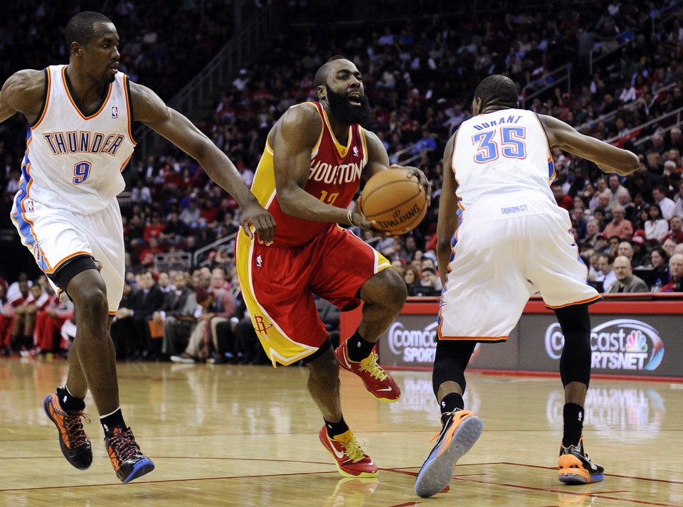 Houston Rockets\' James Harden (13) heads for the basket between Oklahoma City Thunder\'s Serge Ibaka (9) and Kevin Durant (35) in the second half of an NBA basketball game, Wednesday, Feb. 20, 2013, in Houston. Harden scored 46 points in the Rockets\' 122-119 win. (AP Photo/Pat Sullivan)