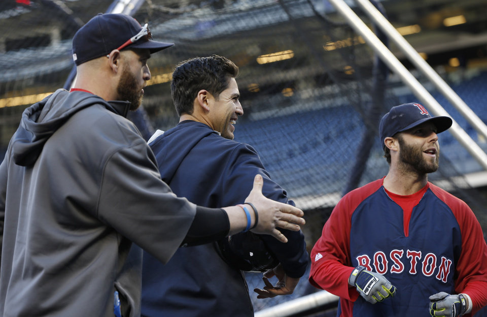 Photo - Boston Red Sox's Jonny Gomes, left, New York Yankees center fielder Jacoby Ellsbury, center, and Red Sox's Dustin Pedroia talk on the tarp before a baseball game at Yankee Stadium in New York, Thursday, April 10, 2014. (AP Photo/Kathy Willens)