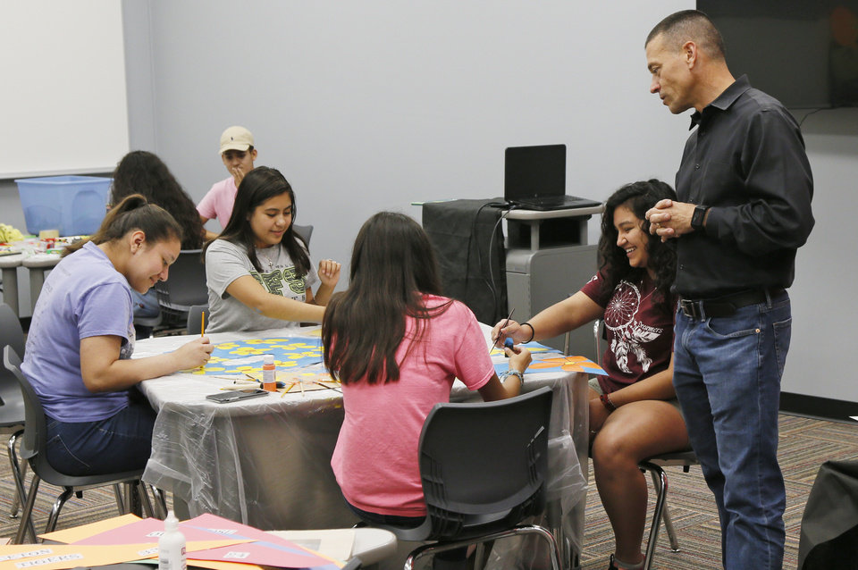 Photo -  Santa Fe South Schools Superintendent Chris Brewster talks with student council members as they prepare for a back-to-school bash Monday inside the new high school building at Plaza Mayor in Oklahoma City. [Photo by Nate Billings, The Oklahoman]