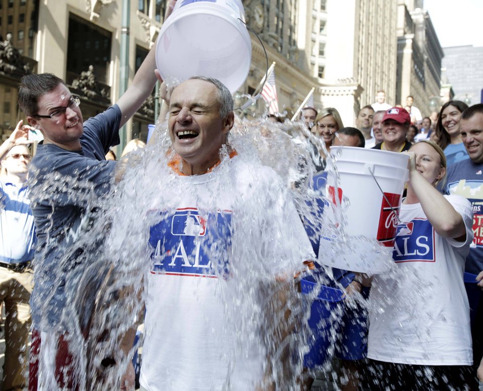 Photo - Major League Baseball Commissioner-elect Rob Manfred participates in the ALS Ice-Bucket Challenge outside the organization's headquarters in New York, Wednesday, Aug. 20, 2014. Manfred participated with more than 160 other MLB employees to raise more than $16,000 for the ALS Association. (AP Photo/Vanessa A. Alvarez)