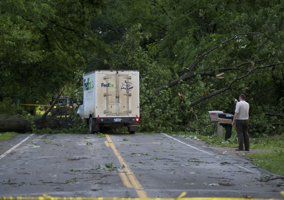 Photo - A man takes a picture after storms on Tuesday, July 1, 2014, in Jackson, Mich. Severe thunderstorms packing high winds knocked down trees and power lines across parts of Michigan, leaving more than 230,000 without power and injuring a firefighter. (AP Photo/The Jackson Citizen Patriot, J. Scott Park) ALL LOCAL TELEVISION OUT; LOCAL TELEVISION INTERNET OUT
