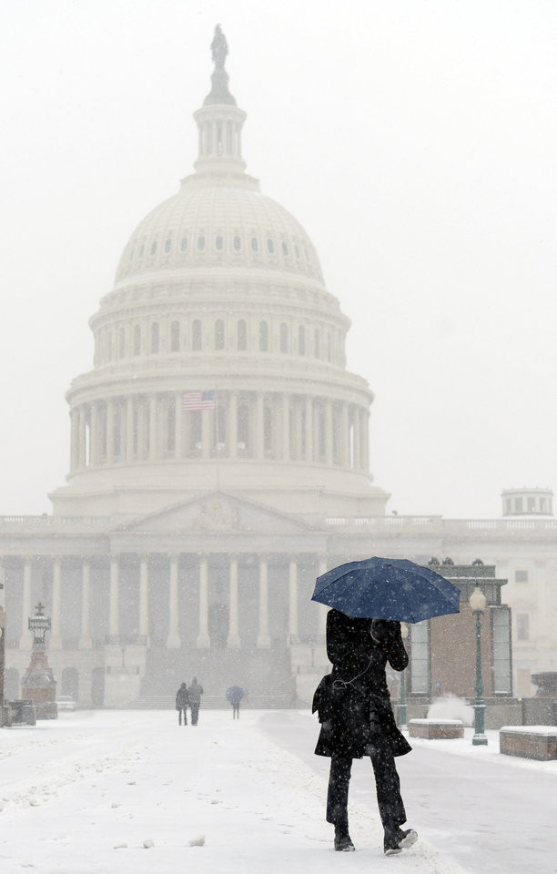 Photo - A pedestrian walks on Capitol Hill in Washington during the start of a major snowstorm, Tuesday, Jan. 21, 2014. Many government offices and schools closed before the first flake of snow, but there were signs Tuesday that significant winter weather was moving into the mid-Atlantic region as heavy snow began falling.(AP Photo/Susan Walsh)