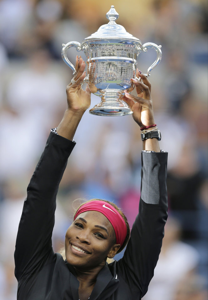 Photo - Serena Williams, of the United States, holds up the championship trophy after defeating Caroline Wozniacki, of Denmark, during the championship match of the 2014 U.S. Open tennis tournament, Sunday, Sept. 7, 2014, in New York. (AP Photo/Charles Krupa)