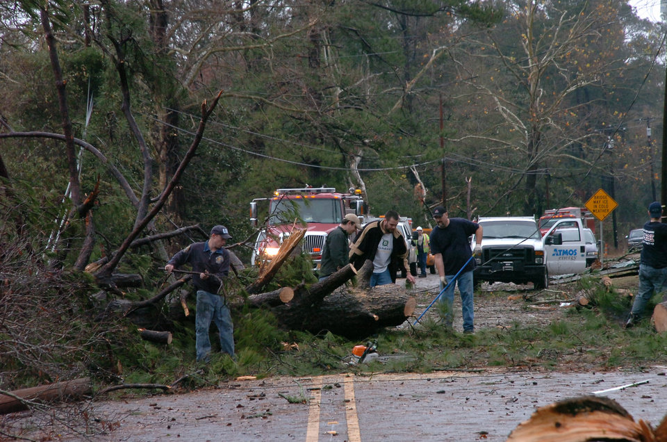 Photo - Members of the Alpine Volunteer Fire Department and the VA Fire Department clear debris from U.S. 71 in the Tioga, La. area, after an apparent tornado tore through the area Tuesday, Dec. 25, 2012. (AP Photo/The Daily Town Talk, Melinda Martinez)  NO SALES