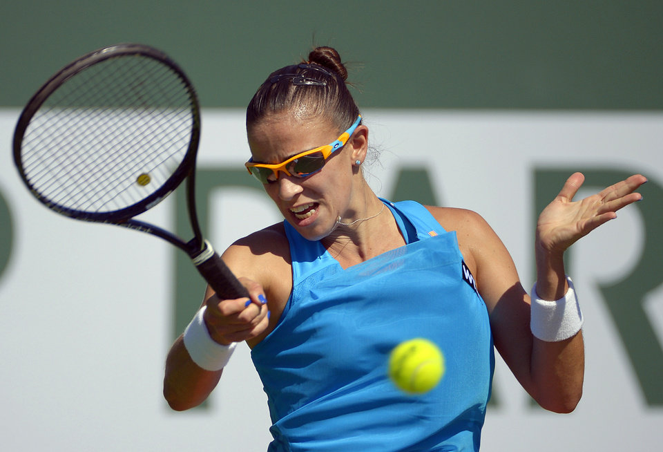 Photo - Paula Ormaechea, of Argentina, returns a shot against Zheng Jie, of China, during a first round match at the BNP Paribas Open tennis tournament, Thursday, March 6, 2014, in Indian Wells, Calif. (AP Photo/Mark J. Terrill)