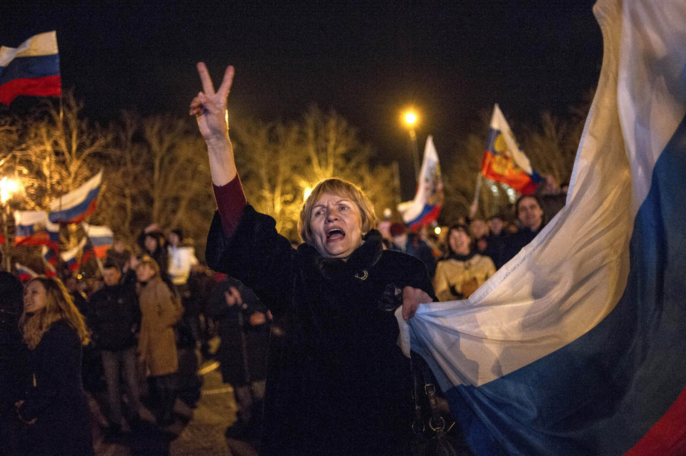 Photo - Pro-Russian people celebrate in the central square in Sevastopol, Ukraine, late Sunday, March 16, 2014. Russian flags fluttered above jubilant crowds Sunday after residents in Crimea voted overwhelmingly to secede from Ukraine and join Russia. The United States and Europe condemned the ballot as illegal and destabilizing and were expected to slap sanctions against Russia for it.(AP Photo/Andrew Lubimov)