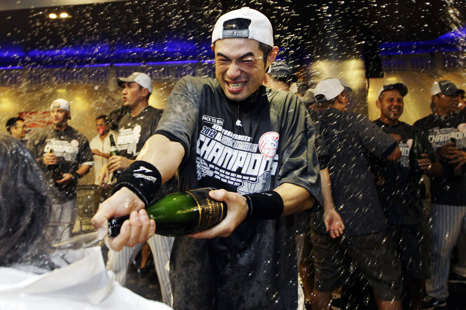 Photo -   New York Yankees' Ichiro Suzuki douses the team photographer as teammates celebrate in the clubhouse after their 14-2 win over the Boston Red Sox in a baseball game and clinched the American League East title at Yankee Stadium in New York, Wednesday, Oct. 3, 2012. (AP Photo/Kathy Willens)