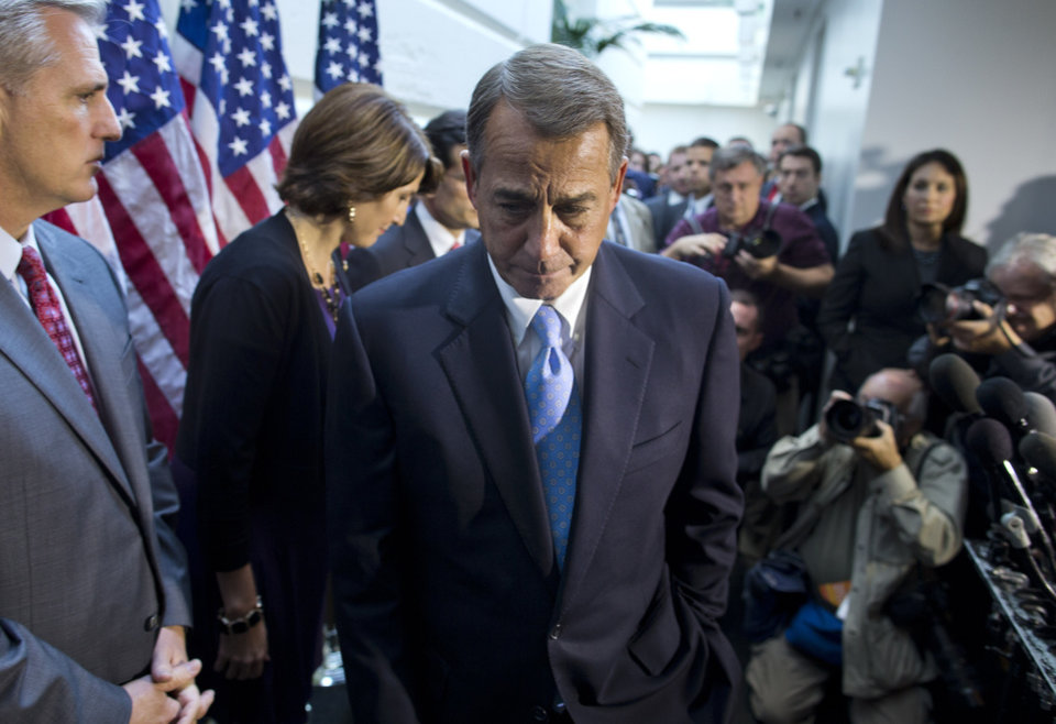 Photo - House Speaker John Boehner, R-Ohio, walks away from the microphone during a news conference after a House GOP meeting on Capitol Hill,  Tuesday, Oct. 15, 2013, in Washington. House GOP leaders Tuesday floated a plan to fellow Republicans to counter an emerging Senate deal to reopen the government and forestall an economy-rattling default on U.S. obligations. But the plan got mixed reviews from the rank and file, and it was not clear whether it could pass the chamber. (AP Photo/ Evan Vucci)