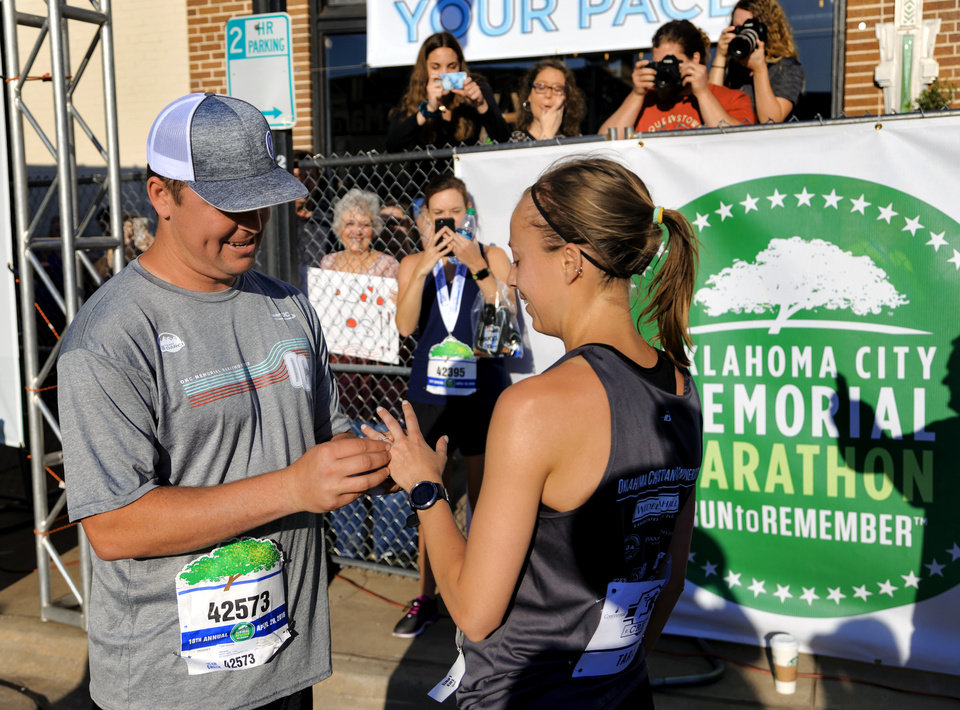 Photo - Tyler Grimes puts the engagement ring on Tara Lewis' finger as he proposed after she crossed the finish line to complete the half marathon during the Oklahoma City Marathon in Oklahoma City, Okla. on Sunday, April 29, 2018.  . Photo by Chris Landsberger, The Oklahoman
