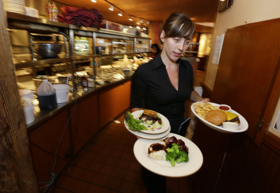 Photo - In this June 2, 2014 photo, Wendy Harrison, a waitress at the icon Grill in Seattle, carries food to a table as she works during lunchtime. An Associated Press comparison of the cost of living at several other major U.S. cities found that a $15 minimum wage, like Seattle adopted this week, will make a difference, but won't buy a lavish lifestyle. (AP Photo/Ted S. Warren)