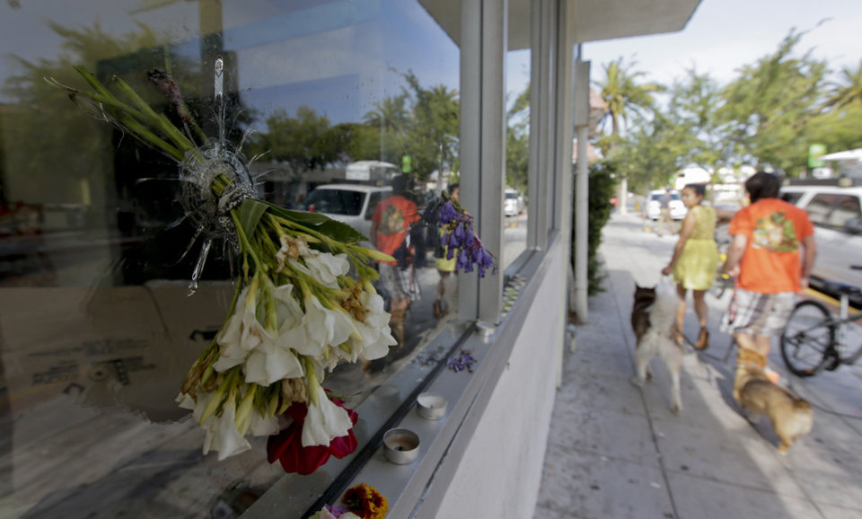 Photo - Flowers are placed through a bullet hole on a window of IV Deli Mart, where part of Friday night's mass shooting took place, on Sunday, May 25, 2014, in the Isla Vista beach community of Santa Barbara, Calif. Sheriff's officials said Elliot Rodger, 22, went on a rampage near the University of California, Santa Barbara, stabbing three people to death at his apartment before shooting and killing three more in a crime spree through a nearby neighborhood. (AP Photo/Chris Carlson)