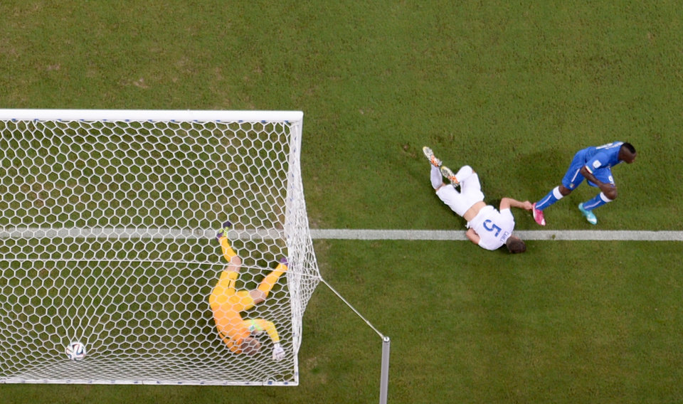 Photo - Italy's Mario Balotelli, right, scores his side's 2nd goal past England's goalkeeper Joe Hart, left, during the group D World Cup soccer match between England and Italy at the Arena da Amazonia in Manaus, Brazil, Saturday, June 14, 2014.  (AP Photo/Francois Xavier Marit, pool)