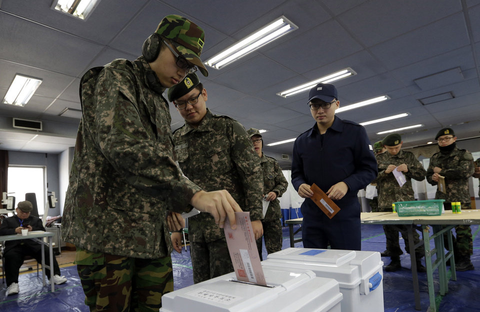 Photo - South Korean soldiers cast their absentee votes for the presidential election at a local polling station in Seoul, South Korea, Thursday, Dec. 13, 2012. South Korea's presidential election is scheduled for Dec. 19. (AP Photo/Lee Jin-man)