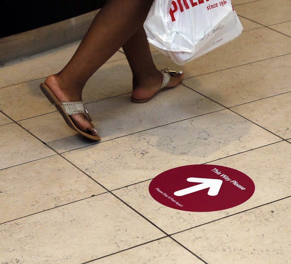 Photo - A woman walks past a sign on the floor directing foot traffic at Penn Square Mall during the re-opening of the mall after being closed because of the coronavirus pandemic, in Oklahoma City, Friday, May 1, 2020. [Nate Billings/The Oklahoman]
