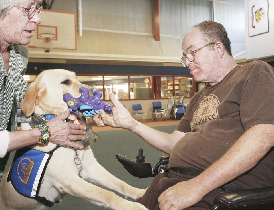 Photo - Vietnam Marine veteran Dale Bruyere works with Ascot, a therapy dog, with creative arts therapist Dawn Truby on Thursday at the VA Medical Center.  PHOTO By  David McDaniel,  The Oklahoman