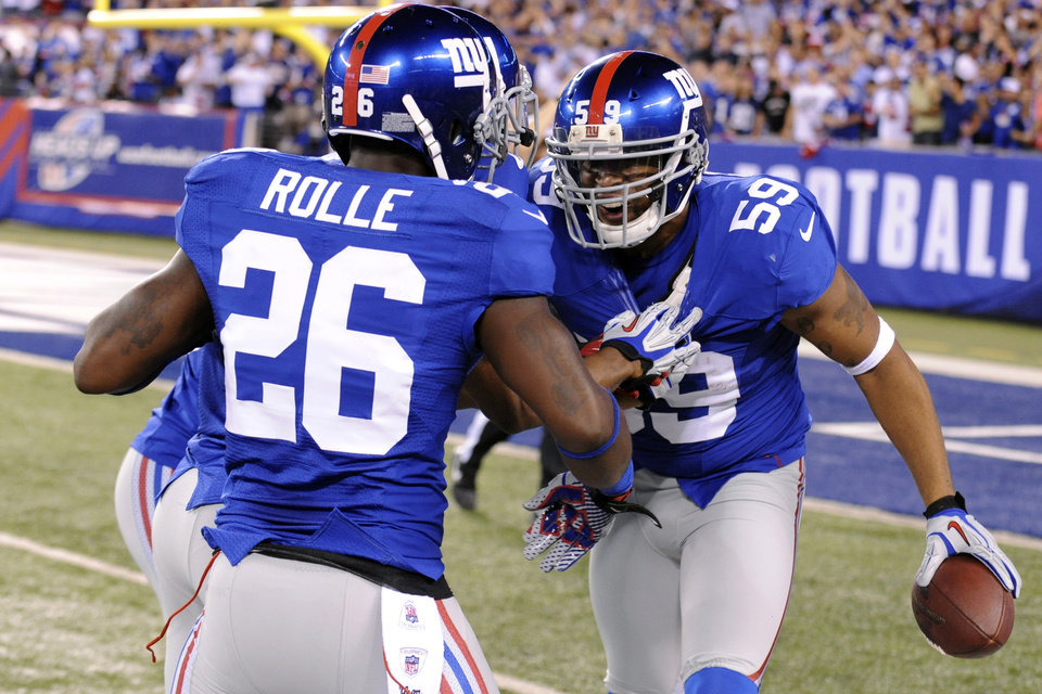 Photo -   New York Giants linebacker Michael Boley (59) celebrates with Antrel Rolle (26) after intercepting a pass during the first half of an NFL football game against the Dallas Cowboys, Wednesday, Sept. 5, 2012, in East Rutherford, N.J. (AP Photo/Bill Kostroun)