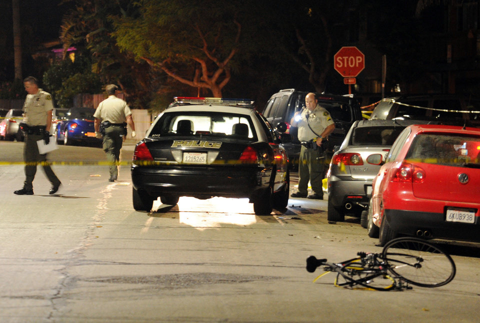 Photo - In this image provided by the Santa Barbara Independent, police investigate the scene after a mass shooting near the campus of the University of Santa Barbara in Isla Vista, Calif., Friday, May 23, 2014. A drive-by shooter went on a rampage near the Santa Barbara university campus that left seven people dead, including the attacker, and others wounded, authorities said Saturday. (AP Photo/Santa Barbara Independent, Paul Wellman) MANDATORY CREDIT