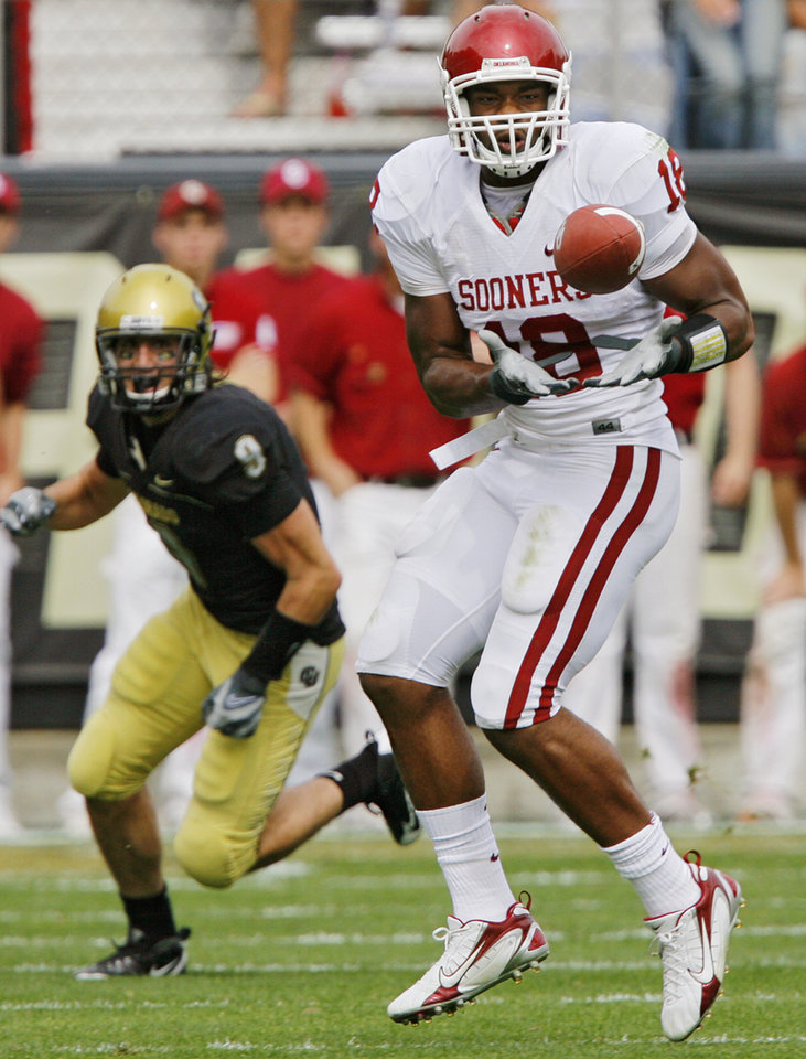 Photo - Oklahoma's Jermaine Gresham (18) catches a pass in front of Colorado's Daniel Dykes (9) during the first half of the college football game between the University of Oklahoma Sooners (OU) and the University of Colorado Buffaloes (CU) at Folsom Field on Saturday, Sept. 28, 2007, in Boulder, Co. 