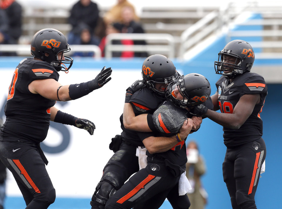 OSU celebrates a touchdown during the Heart of Dallas Bowl football game between the Oklahoma State University (OSU) and Purdue University at the Cotton Bowl in Dallas, Tuesday,Jan. 1, 2013. Photo by Sarah Phipps, The Oklahoman