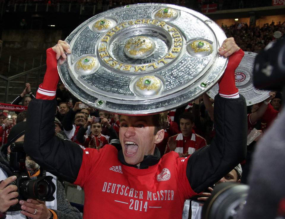 Photo - Bayern's Thomas Mueller lifts a mock champions trophy after the German Bundesliga soccer match between Hertha BSC Berlin and Bayern Munich in Berlin, Germany, Tuesday, March 25, 2014. (AP Photo/Michael Sohn)
