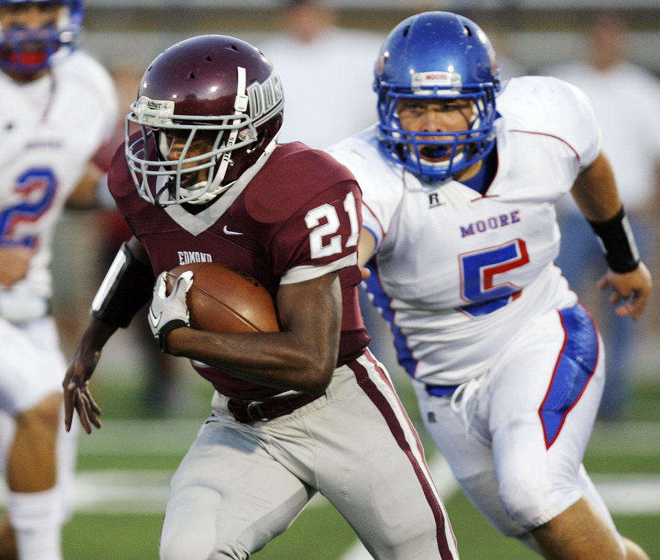 Daniel Smith (21) of Edmond Memorial runs away from Taylor Lewis (5) of Moore during a high school football game between Edmond Memorial and Moore at Wantland Stadium in Edmond, Okla., Thursday, Sept. 29, 2011. Photo by Nate Billings, The Oklahoman