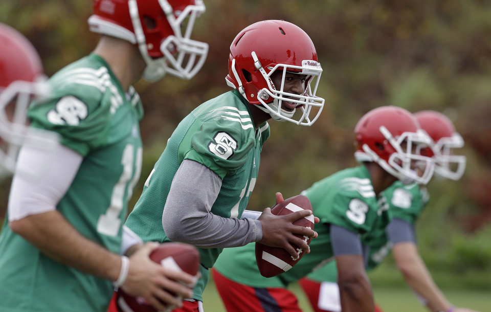 Photo - North Carolina State quarterback Jacoby Brissett, center, and other quarterbacks participate in a drill during the team's first NCAA college football practice of the season in Raleigh, N.C., Saturday, Aug. 2, 2014. (AP Photo/Gerry Broome)