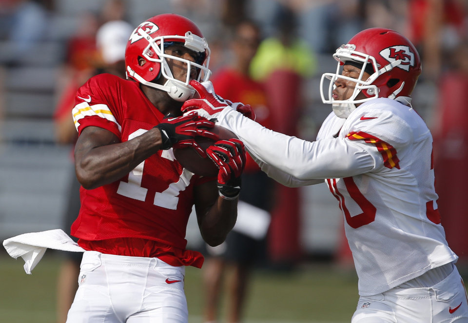 Kansas City Chiefs wide receiver Donnie Avery (17) makes a catch while covered by defensive back Jalil Brown (30) during NFL football training camp in St. Joseph, Mo., Thursday, Aug. 1, 2013. (AP Photo/Orlin Wagner)