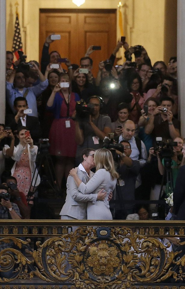 Photo - Kris Perry, foreground left, kisses Sandy Stier as they are married at City Hall in San Francisco, Friday, June 28, 2013. Stier and Perry were married Friday, June 28, 2013, after a federal appeals court on Friday cleared the way for the state of California to immediately resume issuing marriage licenses to same-sex couples after a 4 1/2-year freeze. (AP Photo/Jeff Chiu)