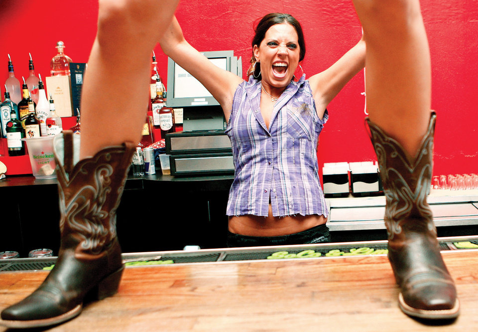 Maria Hurdle gets excited while serving drinks during the opening of Coyote Ugly on Wednesday.  Photo by Ashley McKee, The Oklahoman