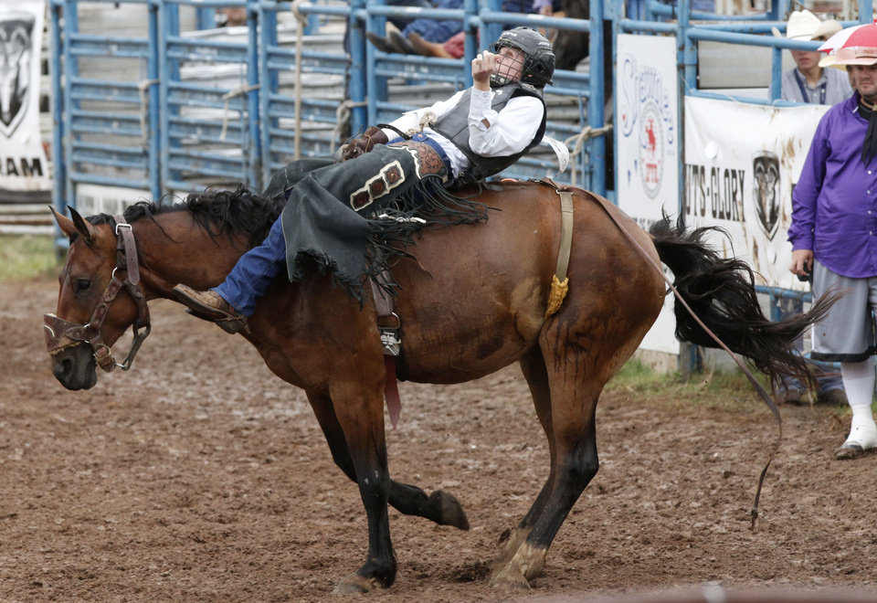 Photo - Taylor Howell, of Warner, competes in the bareback bronc event in   July 10's action at the International Finals Youth Rodeo at the Heart of Exposition Center in Shawnee. Howell has been completely blind since age 2  because of a rare form of cancer known as retinoblastoma.  Photos by Paul Hellstern, The Oklahoman  PAUL HELLSTERN -