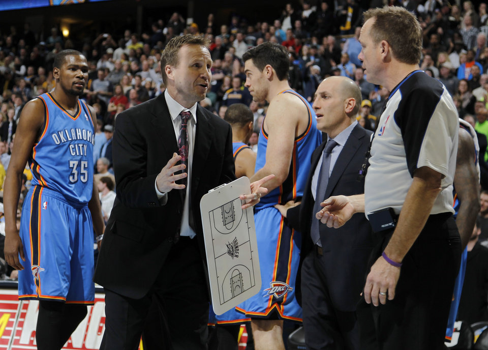 Photo - Oklahoma City Thunder head coach Scott Brooks, center left, argues call against his team with official Zach Zarba in overtime of an NBA basketball game against the Denver Nuggests in Denver on Sunday, Jan. 20, 2013. The Nuggets won 121-118 in overtime. (AP Photo/David Zalubowski) ORG XMIT: CODZ108
